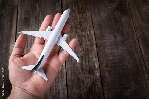 White blank toy of passenger plane on male palm hand over rustic