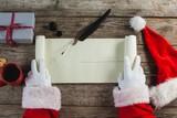 Close-up of santa claus opening scroll