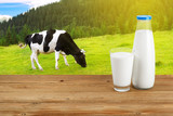 Milk on table with cow on the background