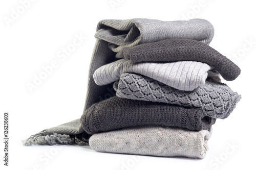 Póster Stack of various sweaters isolated on white background