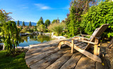 Two Adirondack chairs on a deck overlooking  pond - 126249087