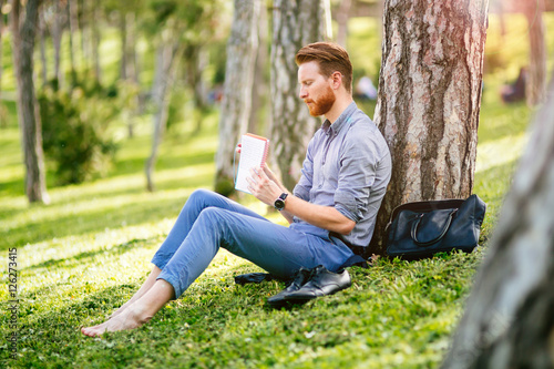 Handsome student reading in nature