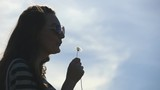 Young woman in glasses want to blowing dandelion seeds, but it does not work.  Emotions of girl during failures. Profile of attractive girl. Blue sky with clouds at background. Slow motion. Close up