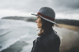 Young hipster traveler girl wearing hat and enjoying beautiful ocean, attractive female tourist traveling along Europe, enjoying freedom and active lifestyle concept
