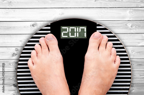 Poster 2017 feet on a weight scale, white wooden floor background