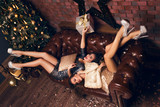 Two  girls lie on the bed in beautiful dress and smiling after Christmas party with presents and laugh to each other. Christmas party. New Year 2017.
