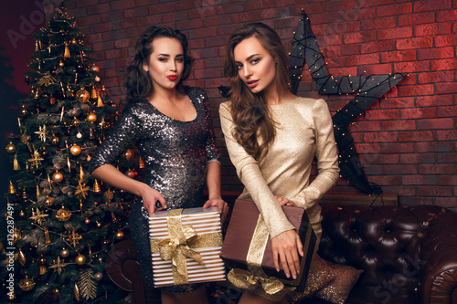 Poster Portrait of two beautiful girl in dress, which give Christmas gifts to each other and smile