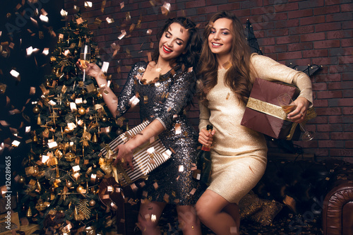Happy New Year to you! Two beautiful young women in a confetti celebration Christmas with a presents and champagne Poster