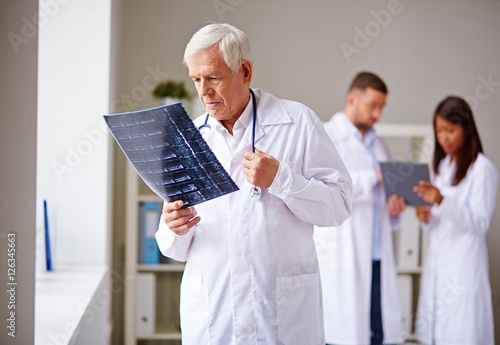 Senior doctor looking carefully at x-ray image, his colleagues working in the ba Poster