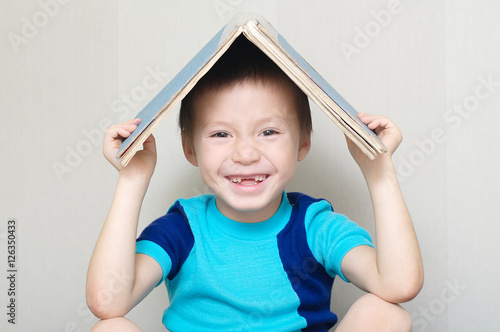 Poster Happy smiling boy with book on head making roof