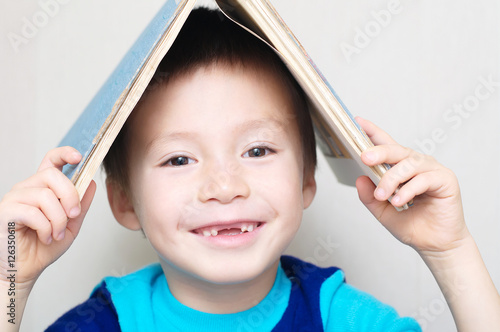 Poster Smiling boy with dropped milk tooth with book on head making roo