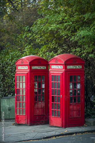 Pair of classic red telephone booths stand under greenery at the edge of a park Poster