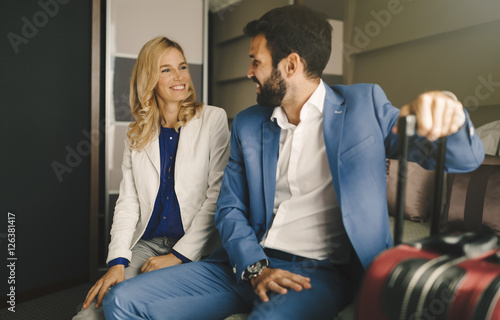 Business couple in formal wear traveling