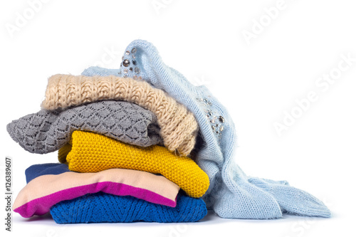 Stack of various sweaters isolated on white background Poster