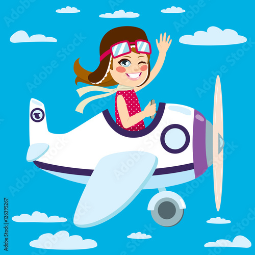 Fototapeta Cute little girl flying a plane on sky waving hand