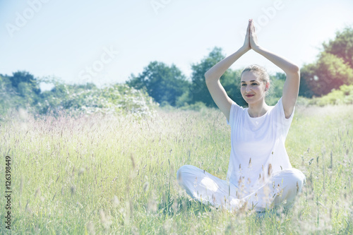 smiling young yoga woman sitting with hands above her head