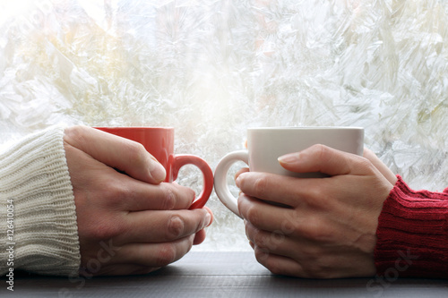 spend  time together warming favorite drink/ two people hold red and white cup across from a window with frost