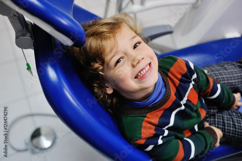 baby boy with curly red hair in blue dental chair. Children's dentist - 126474296