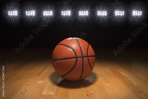 Basketball on wood floor beneath bright lights Poster