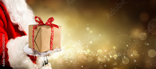 A Present For Christmas - Vintage Golden Background With Santa Claus Giving Gift
