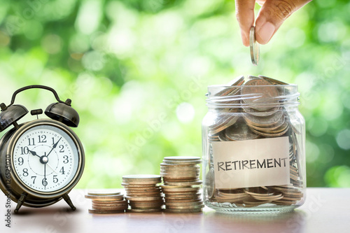 Hand putting Coins in glass jar with retro alarm clock , retirement