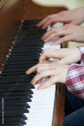 Poster Close Up Of Boy Playing Piano Duet With Teacher