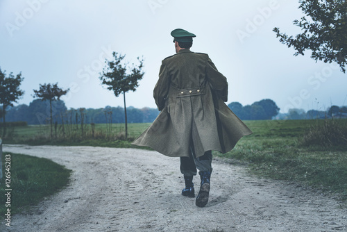 Poster Rear view of vintage 1940s military officer walking on rural roa