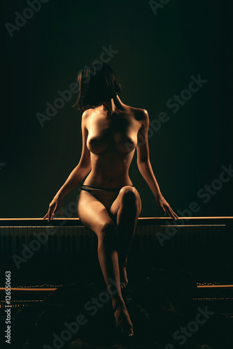 Poster sexy naked woman on old piano