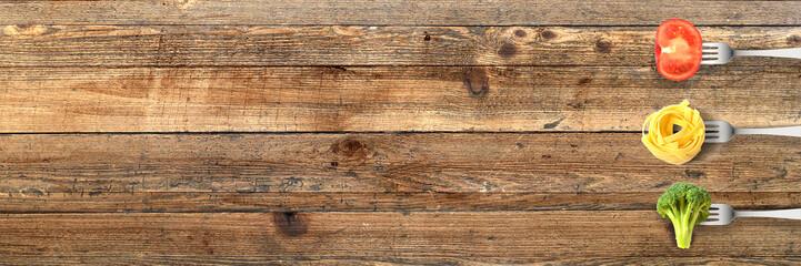 Gemüse und Pasta mit Gabeln auf Holztisch - Banner mit Textfreiraum