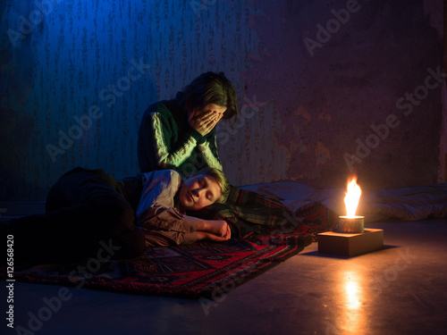 Adult woman sitting on the floor and crying and the young boy sleeping on her la Poster