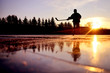 Reflexion of young hockey player on bright natural ice during colorful calm winter sunset on january frozen lake