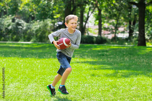 Fotobehang Voetbal Boy Running With Rugby Ball