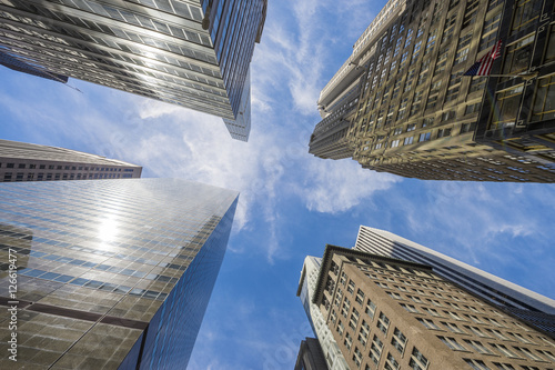 Abstract city skyline view from below looking up to blue sky between an intersection of skyscrapers - 126619477