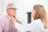 Doctor is examining glands in the neck of her patient.