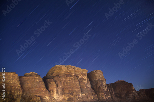 Poster Star trails over desert mountains of Wadi Rum