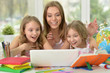 girls  with mother on lesson with laptop