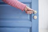 man holding a metal pen in an open wooden door blue - 126666450