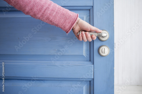 Poster man holding a metal pen in an open wooden door blue