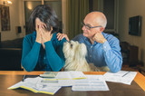 Worried couple with dog reading an important notification in a letter sitting in the living room at home - 126690639