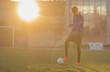 young football player shooting soccer ball. grass field sun, sun