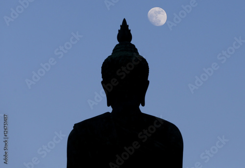 Poster, Tablou A moon shines in a sky over a large silhouetted Buddha statue in Bangkok, Thailand