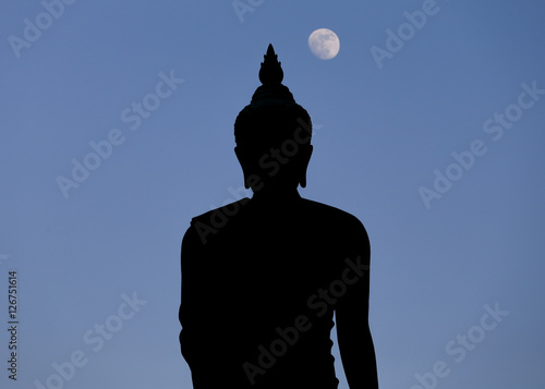 Zdjęcia A moon shines in a sky over a large silhouetted Buddha statue in Bangkok, Thailand