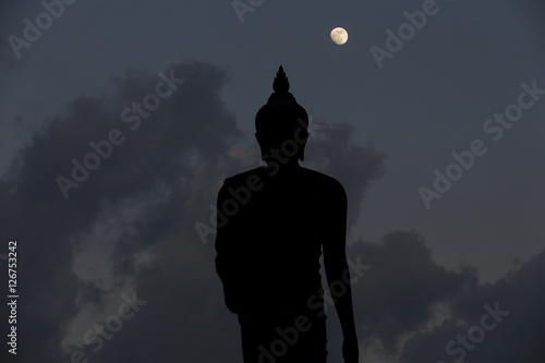 Plagát A moon shines in a sky over a large silhouetted Buddha statue in Bangkok, Thailand