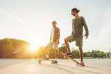 Young people training with longboard with back sun light
