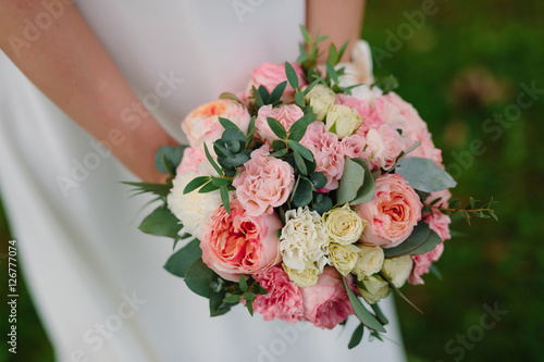 Poster beautiful delicate Bridal bouquet of cream roses in hands of bride