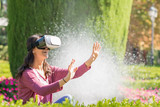 Young happy woman is enjoying with virtual reality glasses in the park
