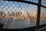Brooklyn Bridge framed in a hole in a fence
