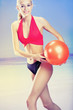 Young beautiful happy smiling blond woman in sportswear playing with red gym ball on sea beach