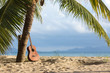 An acoustic guitar standing in the sandy beach under palm tree - 126838090