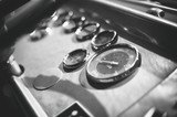 Dashboard inside of old bus cabin. Black and white.